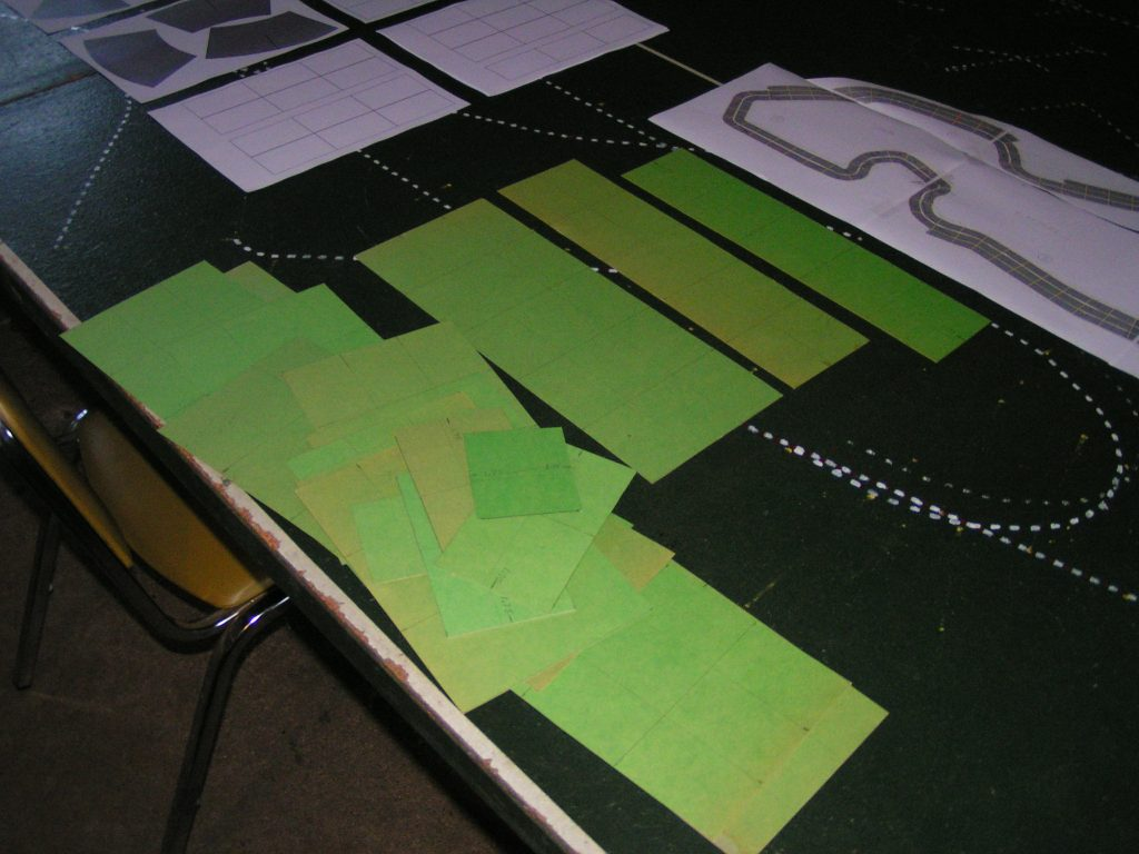 Older green poster-board track template pieces in the foreground.