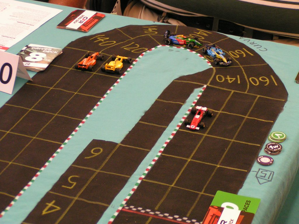 Beckman's Ferrari about to cross the finish line. White and Landis trail, and Cook (yellow car) and Kaluzny (orange car) are side-by-side going into the Parabolica.